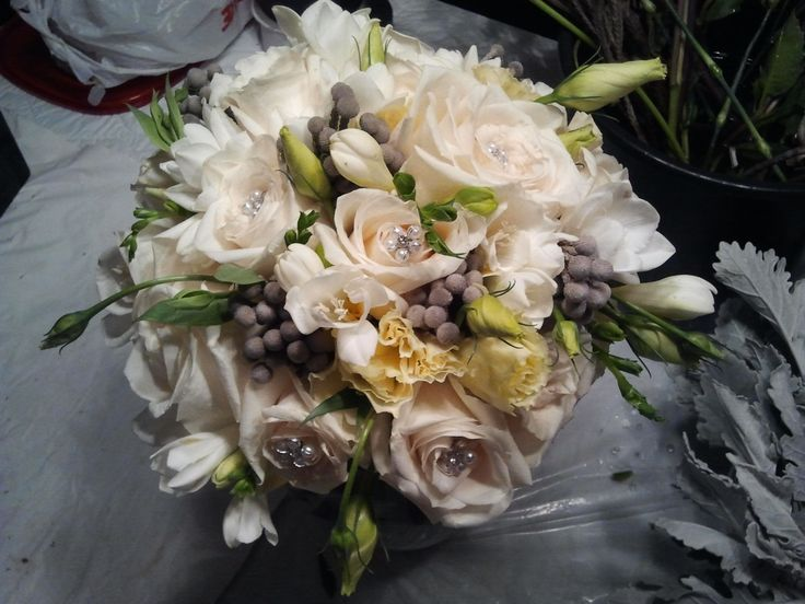 Bridal bouquet of cream roses, freesia, silver brunia with crystal and pearl embellishment -floral creations by Marian Louie, http://www.pinterest.com/marianlouie