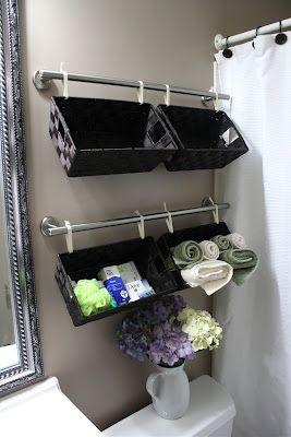 Hang baskets from pretty towel rack with fabric & bows. Small bathroom