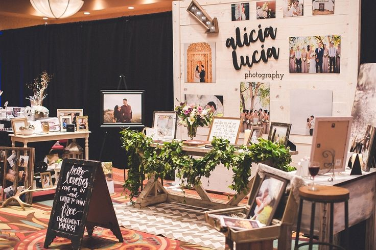 """A glass of wine was a must.""  Wedding show booth inspiration // wedding show booth for photographers // bridal show booth // garland // laser cut logo // weathered wood backdrop"