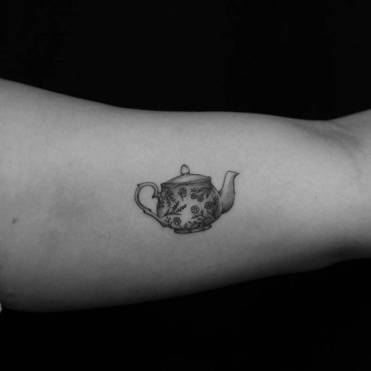 Teapot tattoo on the left inner arm.
