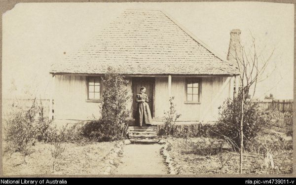 Woman on veranda of slab cottage with shingle roof and front garden, Hill End, New South Wales, ca.1872 [picture].