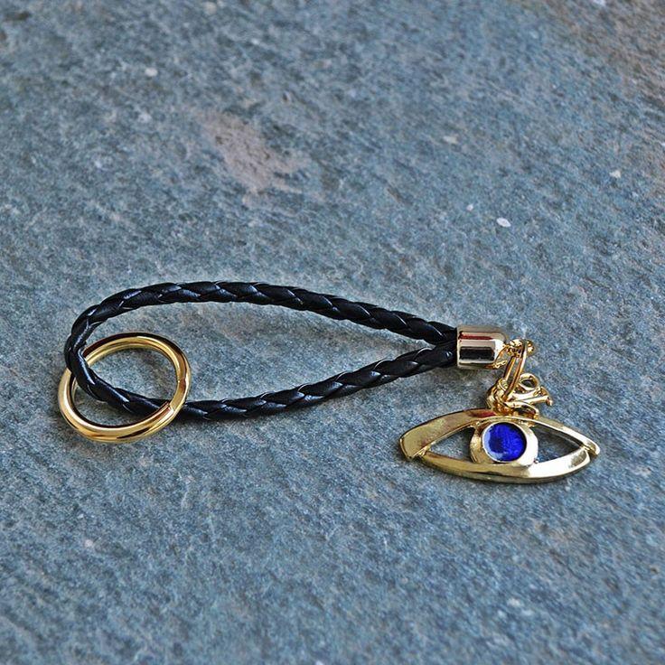 Γούρι μπρελόκ επίχρυσο μάτι, με μαύρο κορδόνι φίδι, επίχρυσο κρίκο και μεταλλικά στοιχεία.