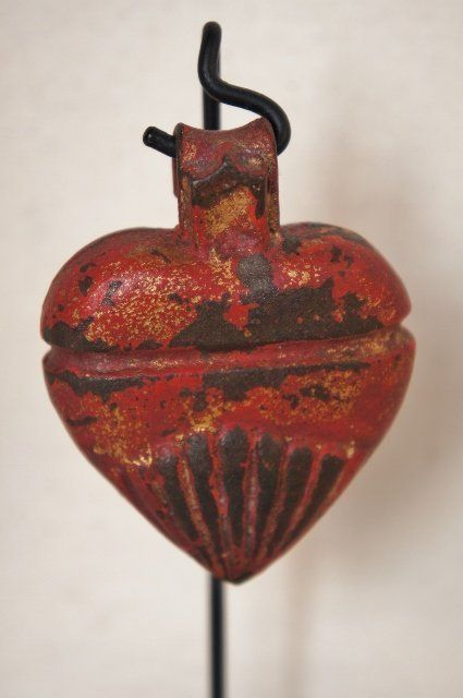 Cast iron gate weight in the form of a heart.