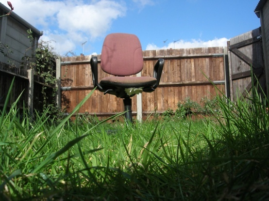 No longer allowed in the home, this neglected older chair is left forgotten in the backyard. The new chair inside getting all of the attention. Please recycle.