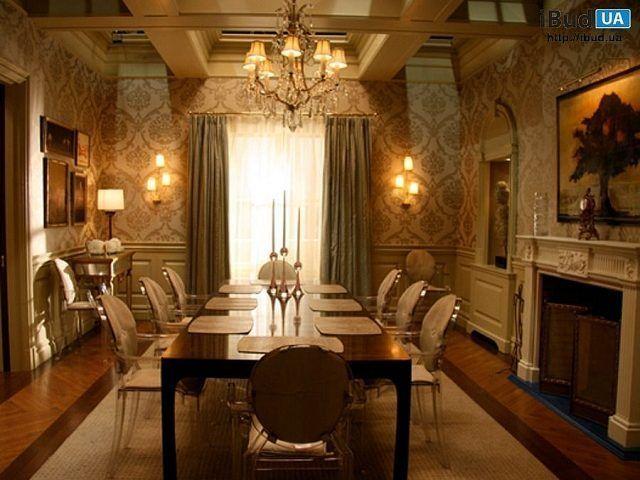 В частном доме сделан дизайн столовой в бежевых тонах. Для облицовки стен используются обои с узором. Нижняя часть стен отделана панелями. Также в комнате сделали фальш-камин, каминную полку исполь...