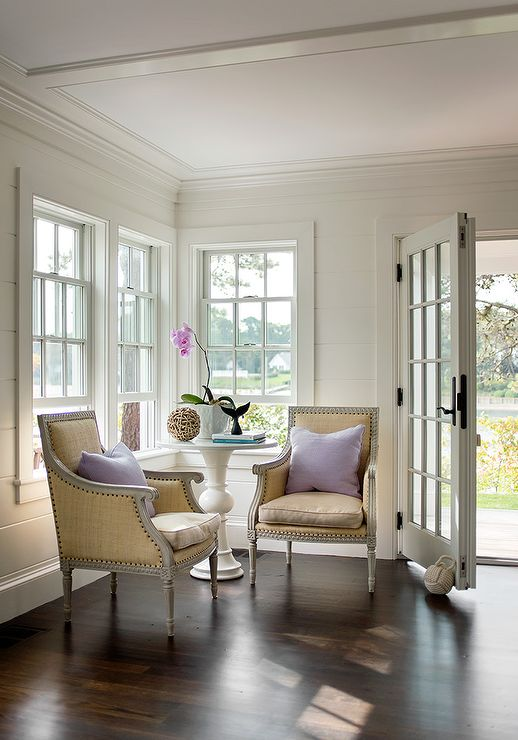 Elegant yet simple foyer features a styled white round marble top pedestal table accent table flanked by Oly Studio Hanna…