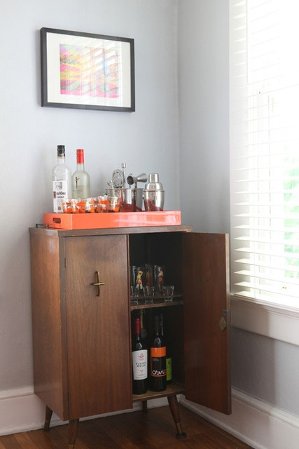Love the liquor cabinet with the bright orange tray on top!
