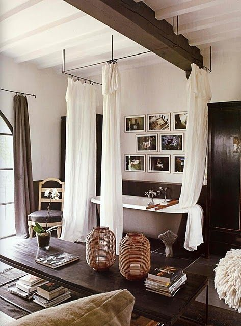 Curtained bath tub in the middle of the bedroom
