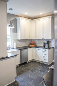 Slate tile floor, white cabinets, dark countertop, white marble backsplash