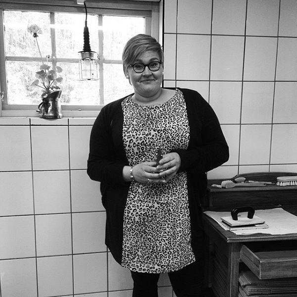 Lena Wiktorsson i Såperiet i Siksjönäs. Kakelväggar och bord för packning i bakrunden. I fönstret bygglampa och perlargon i kopparbytta.