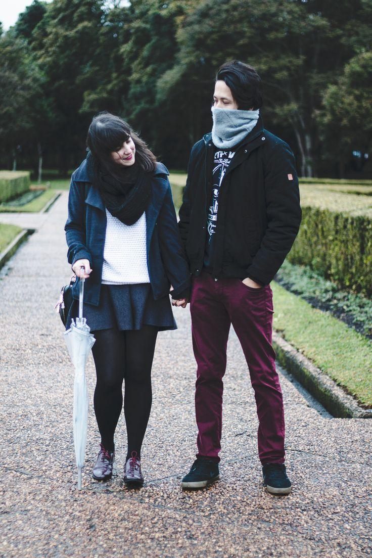 Look confortável de casal de Inverno. Melina Souza com saia de lã cinza escuro, tricô branco, casaco xadrez acinturado, meia-calça preta, oxford borgonha com verniz e bolsa preta com detalhes dourados. Beni com calça borgonha slim fit, moletom com estampa de Darth Vader, casaco preto e gorro cinza médio.