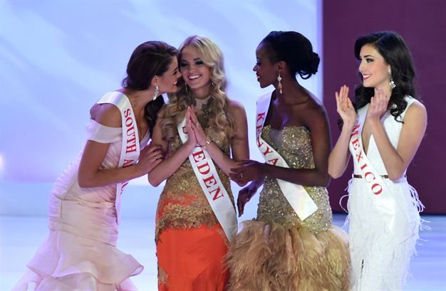 (L-R) Miss South Africa Rolene Strauss, Miss Kenya Idah Nguma and Miss Mexico Daniela Alvarez Reyes congratulate Miss Sweden Olivia Asplund on winning the swimwear fashion section during the grand final of the Miss World 2014 pageant. (Photo by AFP/Leon Neal)