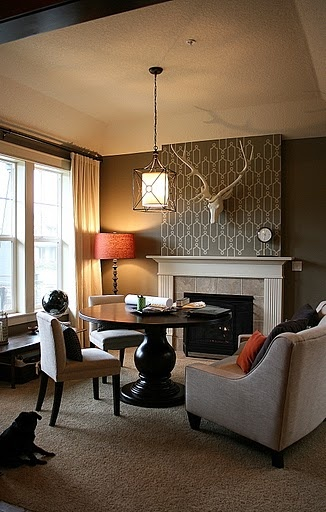 Living room decor -love the little pops of color with lighting and pillow, and a functional table in front of fireplace