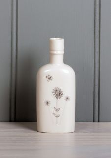 A small porcelain bottle with an illustration of a Somerset flower meadow
