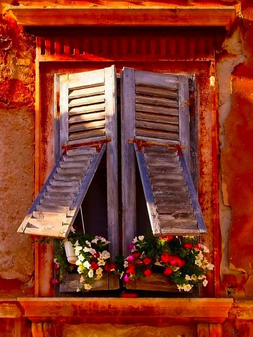 Under open shutters.