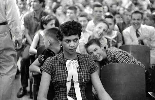 Esta fotografía muestra a Dorothy Counts, la primera joven de color en un instituto solo para blancos.en Estados Unidos en los años sesenta. Puede apreciarse cómo sus compañeros se burlan de ella, la ridiculizan y la abuchean. La foto muestra lo que es el perjuicio, la ignorancia, el racismo, el sexismo y la desigualdad. Pero también muestra la fortaleza, la determinación y la inspiración.