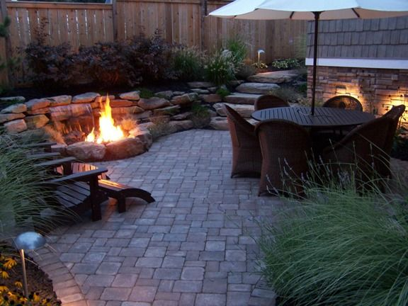 Gas fire pit in front of a waterfall — both passing through a pebble-bed.