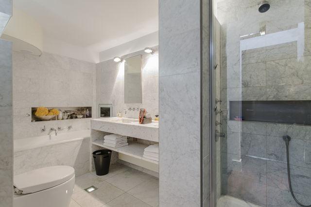 De badkamer; met douche en ligbad met tv