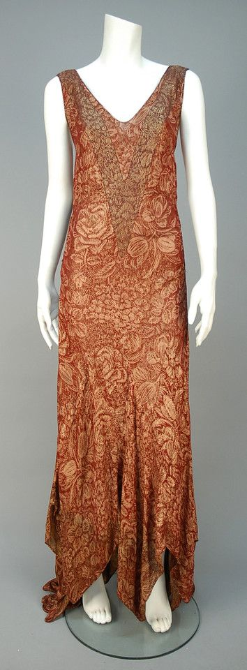 TRAINED METALLIC BROCADE EVENING GOWN, EARLY 1930s  Sleeveless rust silk with dusty rose and gold lame floral, having applied bands to bodice, cutout at center back waist and gored skirt with handkerchief point hem and fishtail train. Unlabeled.  - whitakerauction