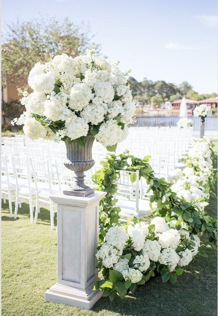 outdoor wedding ceremony featured large and lush traditional urns overflowing with white hydrangea and white stock at the head of the aisle.