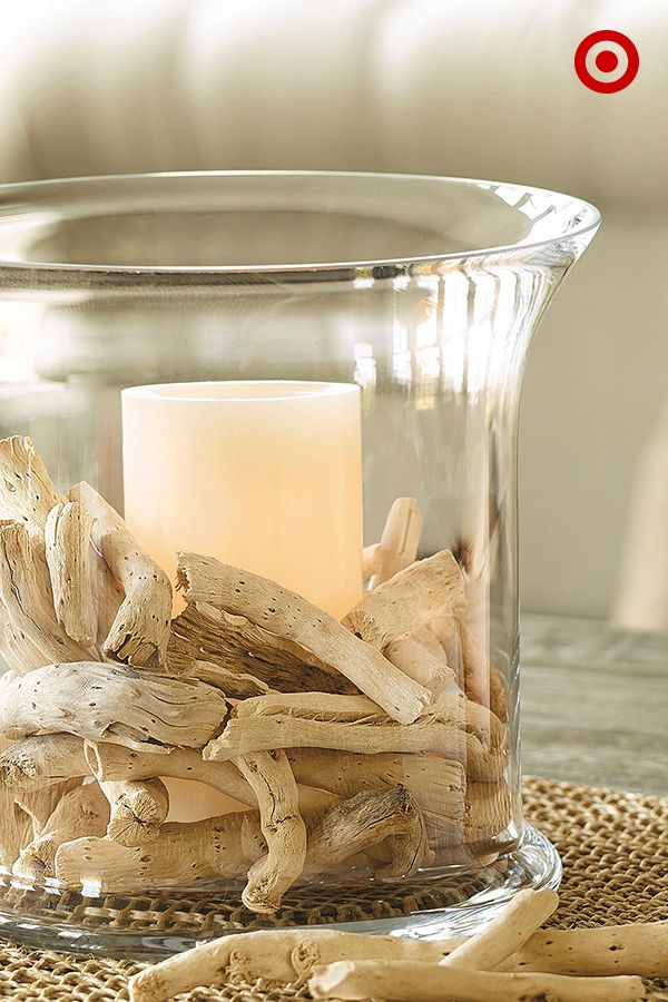 Fill a clear candleholder with pieces of decorative driftwood for a nature-inspired look that evokes beach and seacoast.