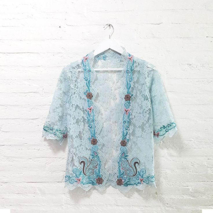 Candy Squirrel Lace 002  IDR 895.000  Open for Pre-Order  Estimated Work Days : 7 – 10 working days  Candy Squirrel Hand Embroidery Contemporary Kebaya Lace  Length of Kebaya : approx. 65 cm  Material used : Fine Lace / Hand Embroidery  Free Size (Bust up to 102 cm)  Length of Sleeve : approx. 38 cm