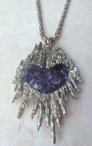 stunning, large, silver molten metal, textured bark spoke purple heart amethyst chip pendant and necklace. The amethyst stone chips are set closely together in the center of the pendant, forming a purple heart, the body of the pendant is formed in silver tone metal in a lovely textured free style, molten metal design, reminiscent of textured bark spokes. The pendant is still on its original silver tone necklace.