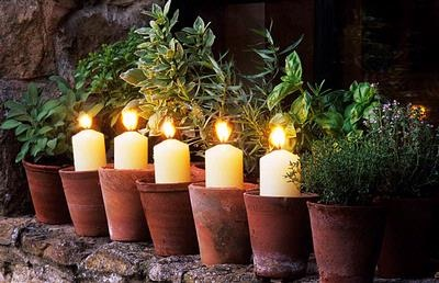 fill the terra cotta planters with sand and stick a candle in it....simple and elegant!