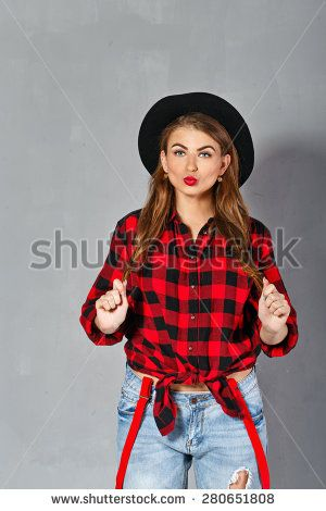Young sexy woman in a hat, plaid shirt and jeans posing in studio, holding her hair and sending a kiss. Girl hipstor. The concept of modern fashion. @shutterstock