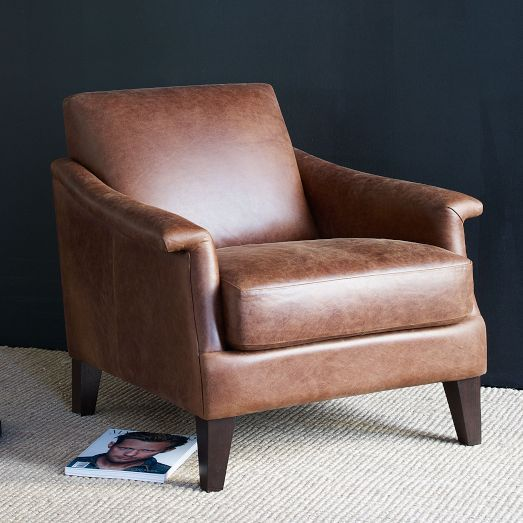 The Writer's Leather Club Chair offers the comfort of a club chair with a smaller footprint, so it works well in compact spaces. Inspired by mid-century silhouettes, it features bent arms and pleated details along the front.