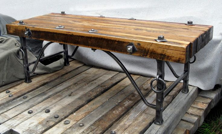 """Wayne Wagstaff, Metal artist.Known as the """"Viking Coffee Table"""",used 6 Recycled / upcycled Australian Hardwood beams (4"""" square by 59"""" long) recovered from the Norwest Train Tunnel construction,with heavy hand forged legs and struts. The beams are cross drilled and held together by two 5/8"""" tie bars.All joints are hand punched and riveted with handmade plates and nuts on Whitworth ½"""" threads.You could use the rings to """"attach"""" your """"pets"""" to; the Coffee table is extremely heavy and hard to…"""