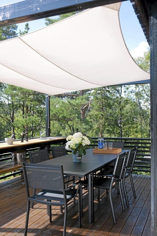 Solseilet skjermer for både sol og trekk på terrassen med det innbydende utekjøkkenet. Her nyter eierne ettermiddags- og kveldssolen uten å måtte forlate terrassen.