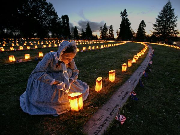 On the anniversary of President Lincoln's 1863 Gettysburg Address, a volunteer in period dress lights luminarias. The candles illuminate markers commemorating soldiers killed at the Battle of Gettysburg.