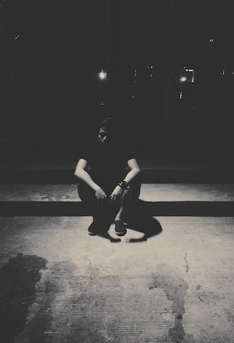 Lonely Man Sitting On Footpath In Dark