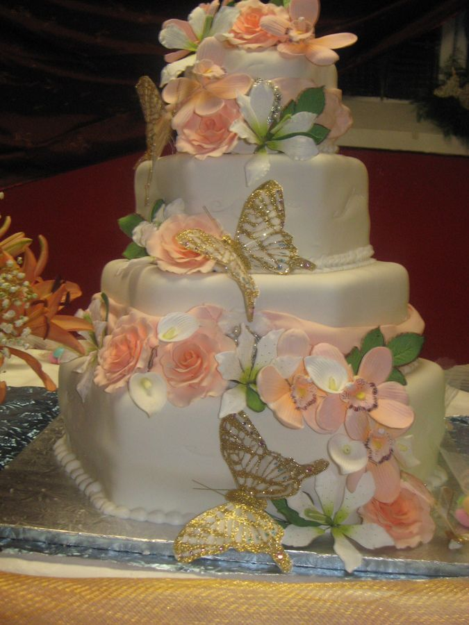 hexagon ivory wedding cake decorated with sugar  paste peach roses, gold butterflies and white lilies ~