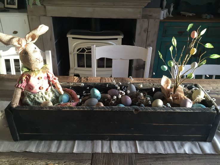 Easter center piece. Rabbit overseeing the Easter eggs in a Rustic wooden box.