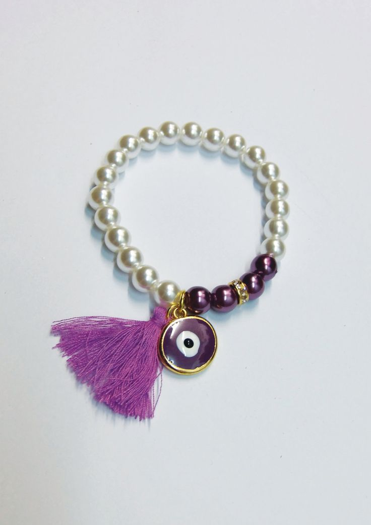 Handmade bracelet/white pearls/purple pearls/base metal round charm/gold plated/24 carats/purple tassel/white crustals/purple enamel/eye by CrownedCharm on Etsy