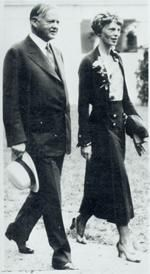 AMELIA EARHART walking with President Hoover on the grounds of the White House; January 2, 1932