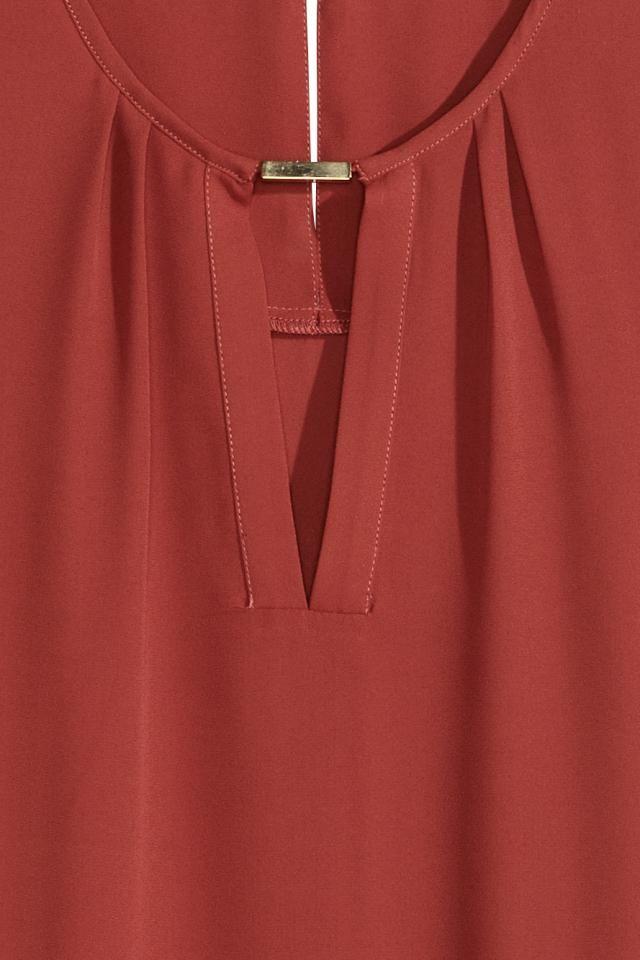 Camicetta senza maniche in tessuto con gioiello in metallo sullo scollo. Apertura sulla schiena con bottone nascosto sulla nuca. Linea arrotondata in basso,