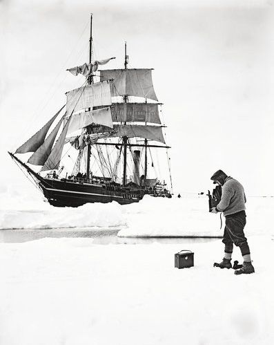 Self-portrait by professional travel photographer Herbert Ponting, hired by Scott, as he photographs the Terra Nova in pack ice, December, 1910.