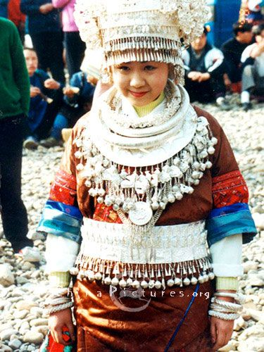 A young Miao girl wears traditional clothes and silver-decked headwear  and jewelry for the Lusheng Festival in southeast Guizhou.