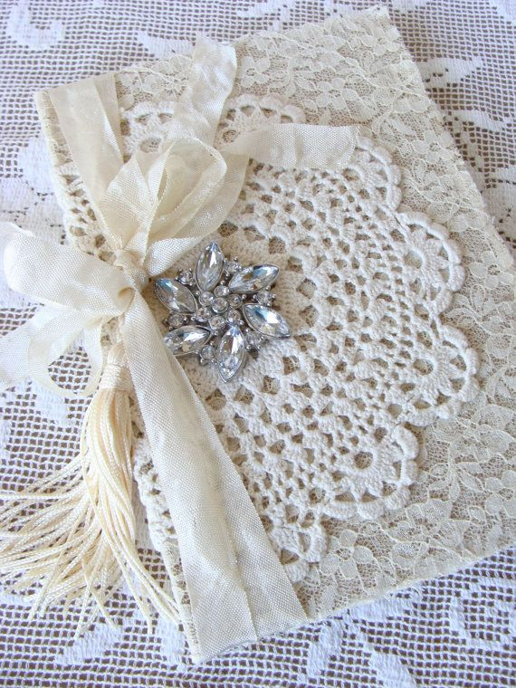 Sweet and shabby vintage inspired hardback book covered in layers of fabric, lace and a vintage doily. A tassel hangs from tattered seam binding