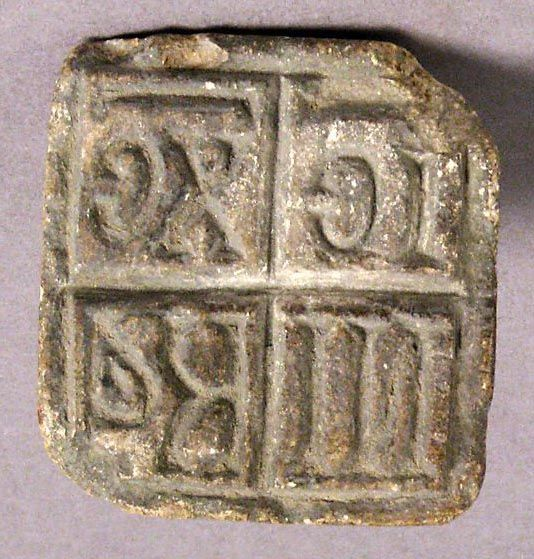 A ceramic Byzantine bread stamp, 500-900, which, when pressed into a loaf of dough, would leave the mark 'Jesus Christ Victorious'; it would hav been used to make the consecrated bread of the Eucharist. (The Metropolitan Museum of Art)