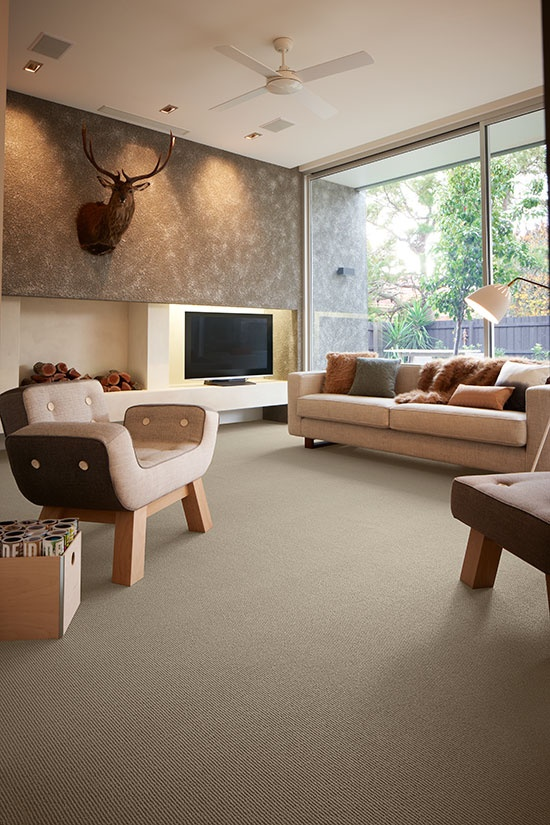 The perfect balance of warmth, comfort and style is created with this pared back look, using a mix of subtle textures from the linear design of the sisal carpet to the concrete textured wall and the soft tactile faux fur cushions and throws.  Credits - Carpet: Godfrey Hirst Carpets; Chair and ottoman: Yellow Diva; Floor Lamp: Great Dane; Cushions and throw: Aura Home.