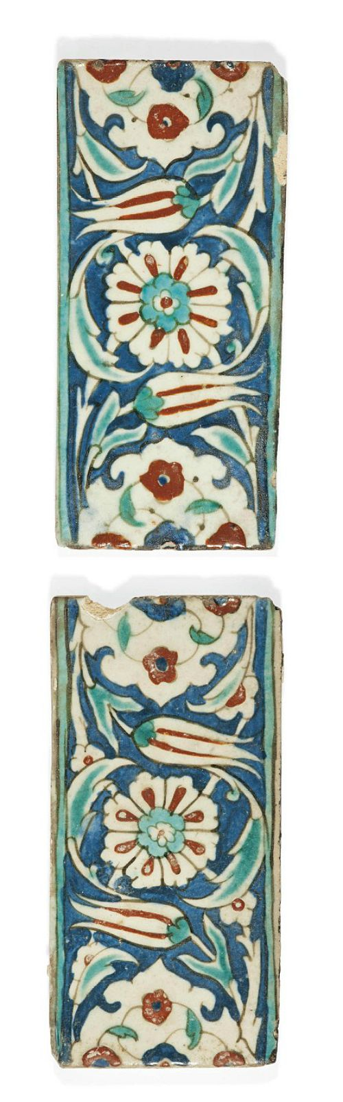 TWO IZNIK POTTERY BORDER TILES  OTTOMAN TURKEY, CIRCA 1600  Each of rectangular form, with design of composite flowers, tulips and scrolling palmettes reserved against cobalt-blue ground, with red highlights, with turquoise-blue borders, small chips, otherwise intact Each 5 x 10 1/8in. (12.8 x 25.7cm.)