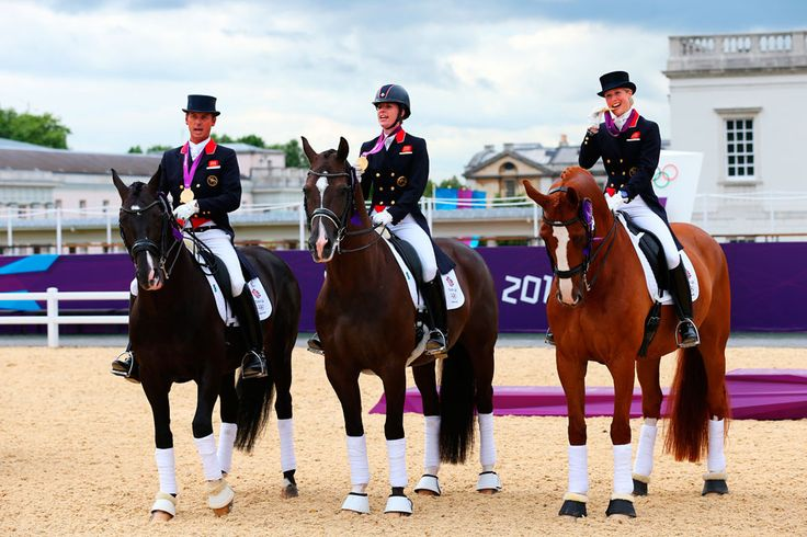 (l-r) Carl Hester on Uthopia, Charlotte Dujardin on Valegro and Laura Bechtolsheimer on Mistral Hojris pose with gold medals for Great Britain in the Team Dressage equestrian event. London Olympics 2012