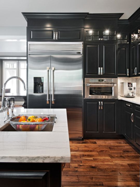 Black cabinets with white granite counters and distressed for Brown kitchen cabinets with black appliances