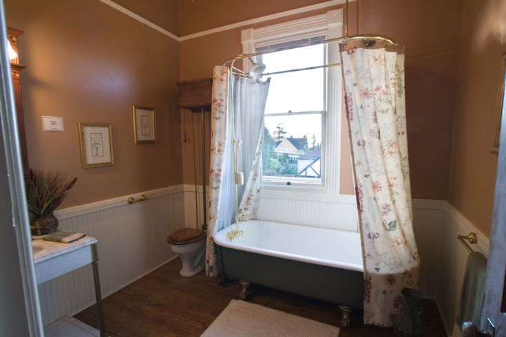 pretty bathroom with claw foot tub and vintage toilet