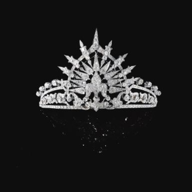 The central fleur-de-lys motif set en tremblant to a tiara composed of foliate and lanceolated motifs, set with cushion-shaped, circular-cut and rose diamonds.