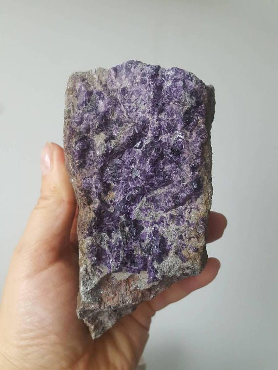 This is a very large, purple fluorite specimen from the Burren, Ireland. This stone was collected in the summer of 2017, it weighs 662g and measures about 13cm ( ca.5 inches). One face of the stone is almost completely covered with beautiful and shiny, bright-purple fluorite. The other faces are raw limestone with patches of red hematite.
